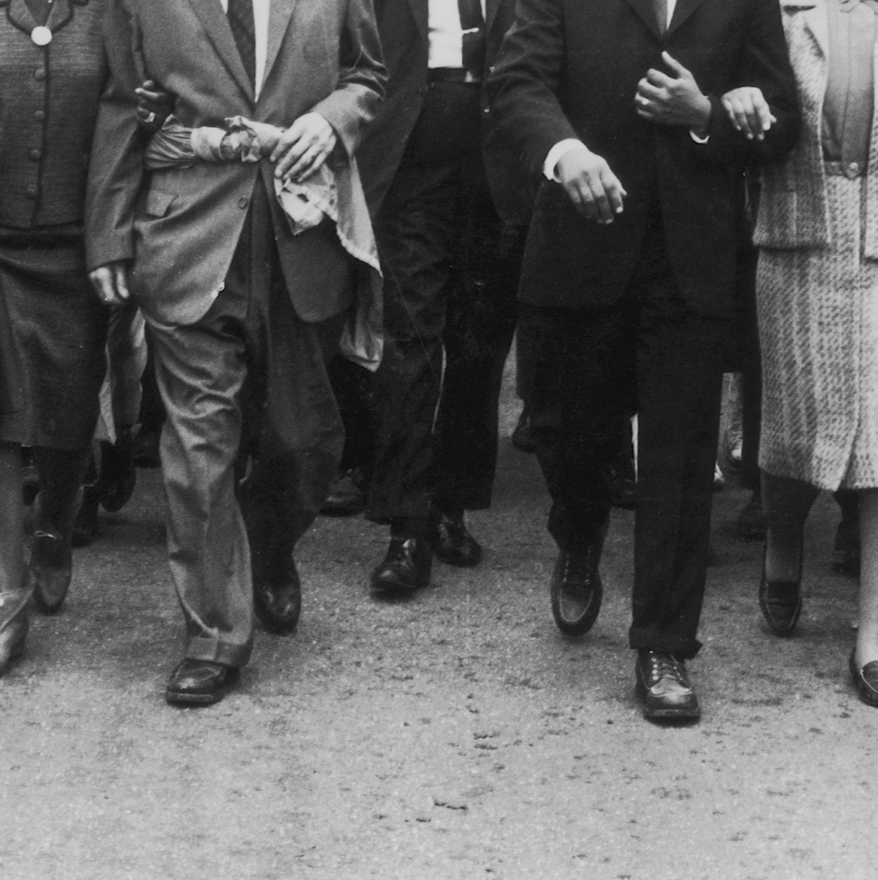 A black and white photograph of men in suits walking
