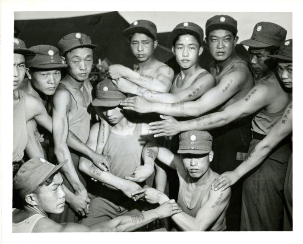 Prisoners of war with anti-communist slogans tattooed on their arms